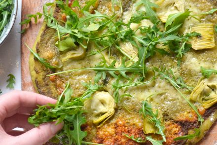 Recipe for homemade pizza dough and pizza verde with pesto, arugula, artichokes, mozzarella and parmesan cheese.
