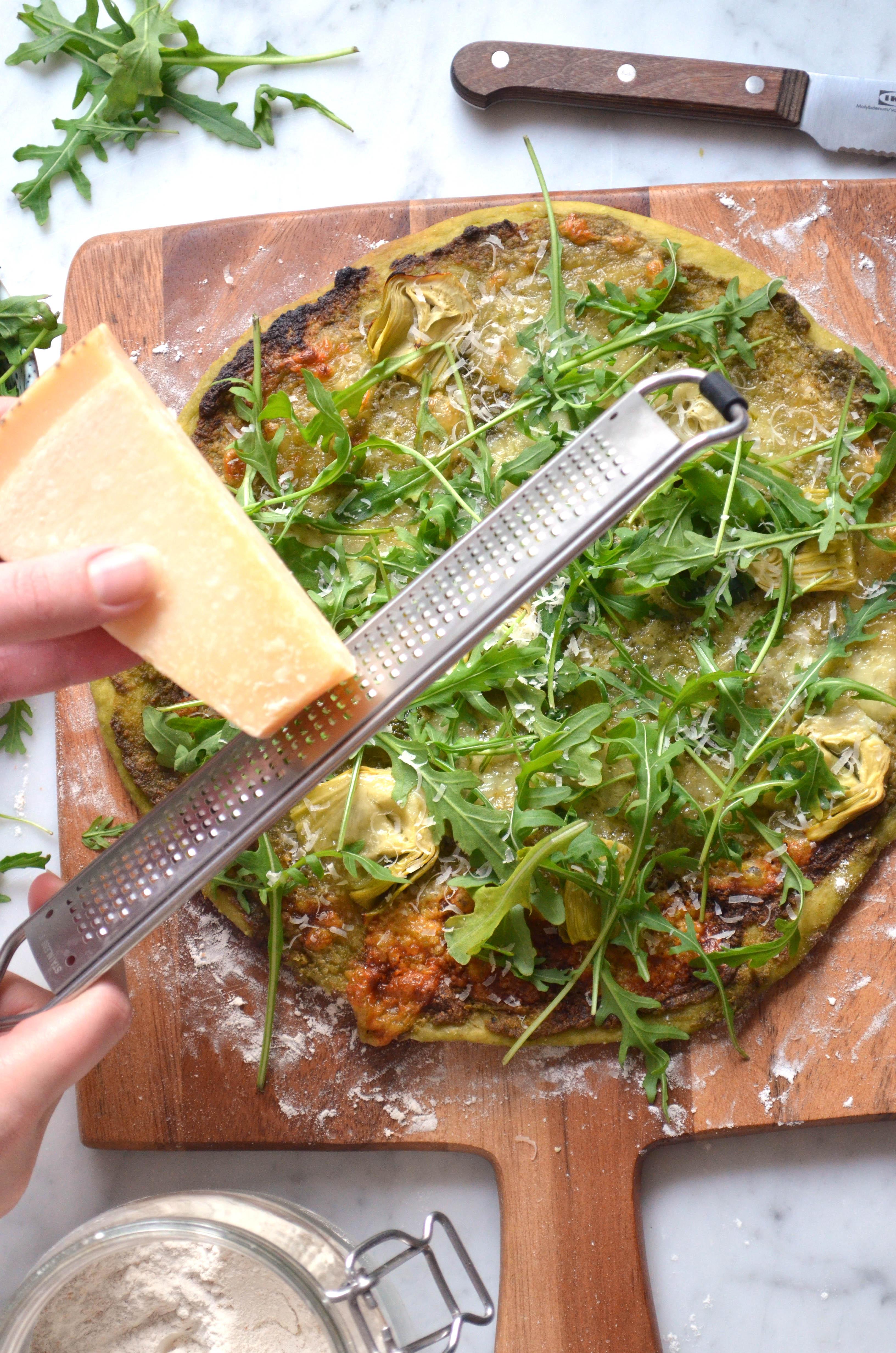 Recipe for homemade pizza dough and pizza verde with pesto, arugula, artichokes, mozzarella and parmesan cheese.